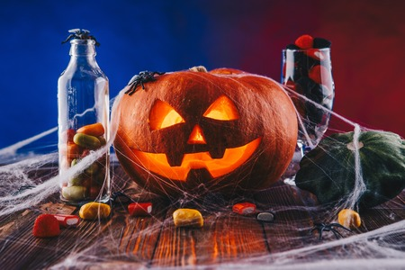Halloween Pumpkin in a spider web with sweets and dark lighting. Trick or treat concept on blue and red background