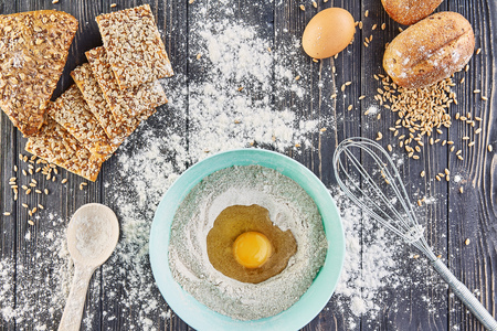 Egg in the flour, bakery ingridients for bread, pizza or pie making ingridients, food flat lay on wooden kitchen table background