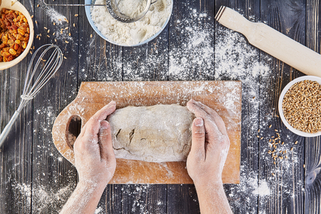 Hands working with dough preparation recipe bread, pizza or pie making ingridients, food flat lay on kitchen table background