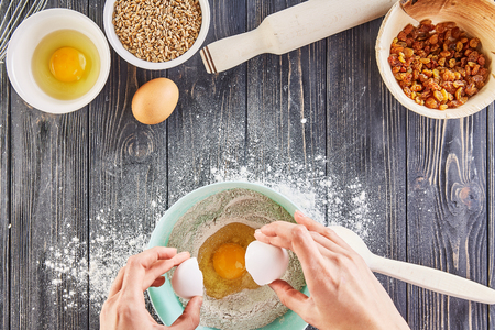 Hands breaking an egg to flour for recipe bread, pizza or pie making ingridients, food flat lay on wooden kitchen table background