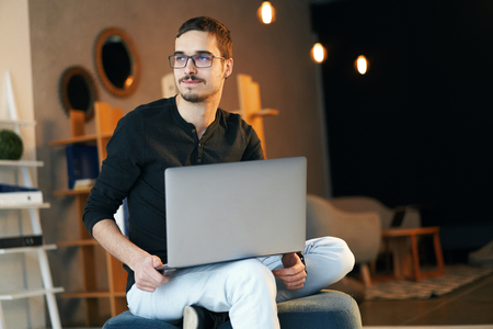 Young man sitting with computer. Freelancer in glasses working with laptop, project manager.