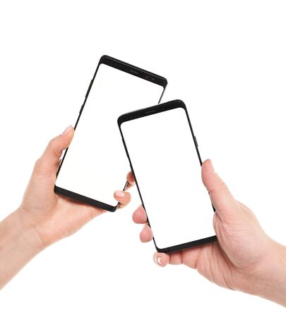 Two hands holding smartphones blank screen with modern frameless design while wireless transferring data NFC connected isolated on white background