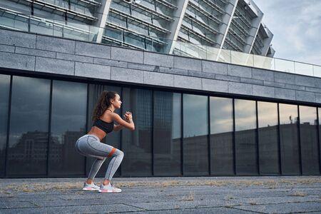 Giovane donna atletica che fa esercizi di squat con gomma sportiva nella posizione urbana della città city