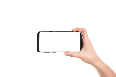 Woman holding with both hands the black smartphone blank screen with modern frameless design isolated on white background