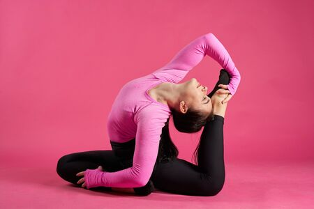 Young athletic woman making yoga and gymnastics stretching exercises on pink background