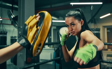 Athletic woman during fight training on boxing ring wearing green bandages on hands, punching exercises with coach Stock Photo