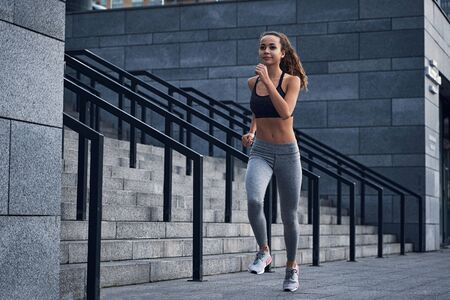 Young athletic woman running at the city stadium with urban stairs background Zdjęcie Seryjne