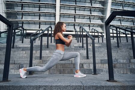 Young athletic woman stretching at the city stadium, training at urban location