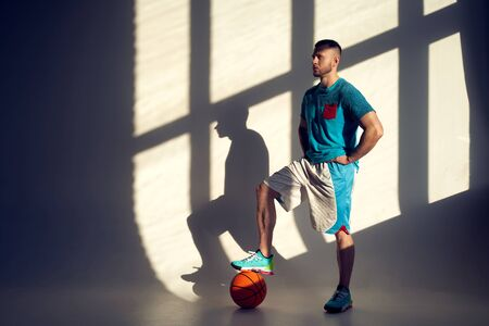 Young athletic man, basketball player holding ball and standing near wall with shadows from window Zdjęcie Seryjne