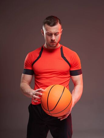 Young athletic man holding basketball ball and looking down on grey background Stock fotó
