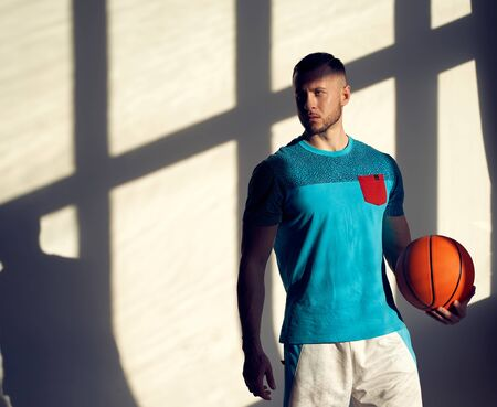 Young athletic man, basketball player holding ball and standing near wall with shadows from window