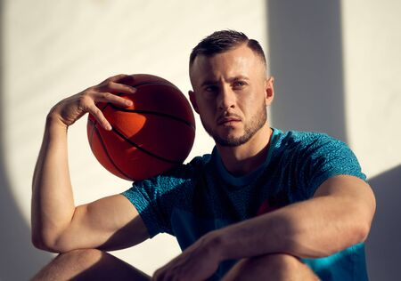Portrait of basketball player holding ball on shoulder and sitting near wall with shadows from window
