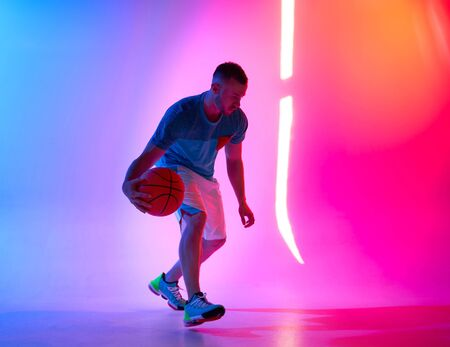 Young athletic man dribbling with basketball ball posing on mix of blue and pink background with light projection