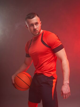 Young athletic man, basketball player posing holding ball in one hand with back lights and smoke on background Zdjęcie Seryjne