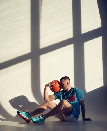 Young athletic man, basketball player holding ball on shoulder and sitting near wall with shadows from window Zdjęcie Seryjne