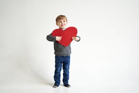 Sweet boy holding red paper heart on white background. Valentines day or kids healthcare, medical concept