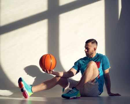 Young athletic man, basketball player holding ball on shoulder and sitting near wall with shadows from window