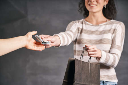 Woman courier giving change to the client or client gives money to the courier