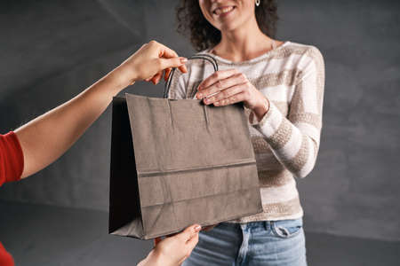 Woman courier giving parcel to client in paper eco bag Archivio Fotografico
