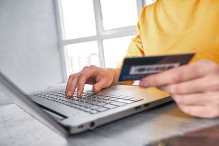 Close up shot of bank card in hand of woman. Shopping online from home