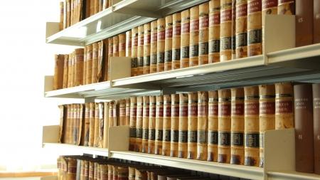 tooled leather: Scaffali carichi di colorato ornato antico cuoio dorato lavorata legato libri in una libreria ad angolo lontano dalla fotocamera
