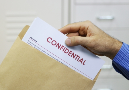 shredding: Cropped view image of a man handling confidential documents placing them inside a brown manilla envelope for mailing