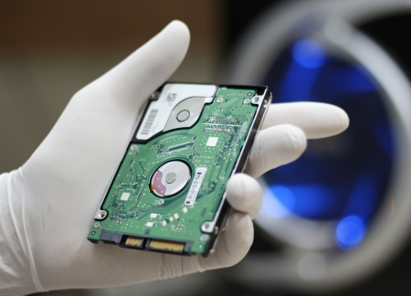 Cropped view of a gloved hand holding a computer hard drive disc in the process of replacing, repairing or stealing it Stock Photo