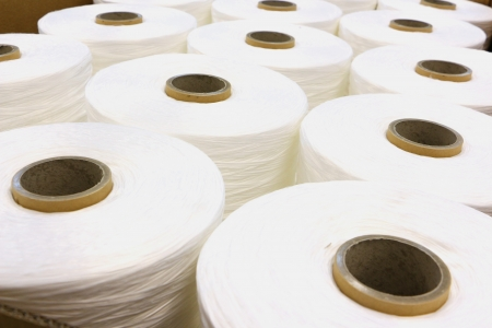 cloth manufacturing: Industrial fabric huge spun yarns with white fabric Stock Photo