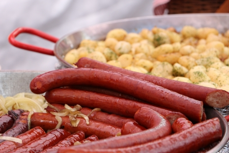 catered: Fried spicy beef and pork sausages in a pan with chopped onion at a catered event or cafeteria