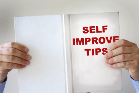 self   improvement: Hands holding a self improvement how to book Stock Photo