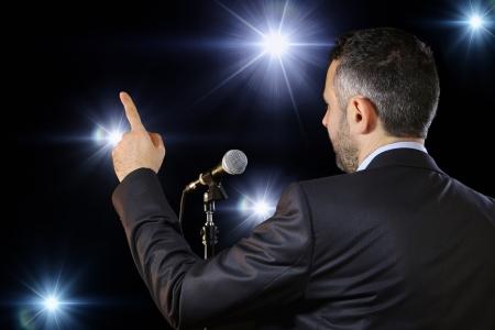 Achter mening van een mannelijke spreker in het openbaar te spreken bij de microfoon, wijzend, in de spotlights, symbool van leiderschap en internationale conferenties