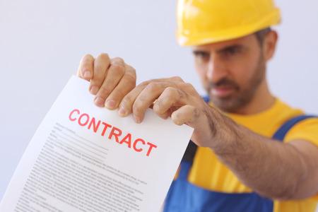 lacrime: Costruttore o operaio in un casco che strappa un contratto che si è tenuta esteso di fronte a lui con attenzione il documento