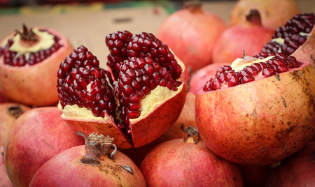 Open red juicy pomegranates in the market photo