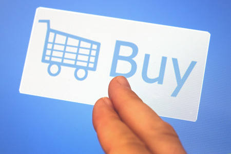 facebook: Mans fingers touching a white Shopping cart and Buy sign on a blue background conceptual of making a purchase during online shopping and e-commerce Stock Photo