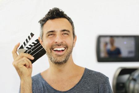 ビデオ制作の映画クラッパーを保持している若い男を設定