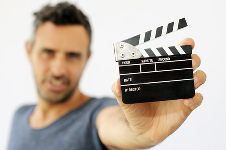 Young man holding movie clapper on white background photo