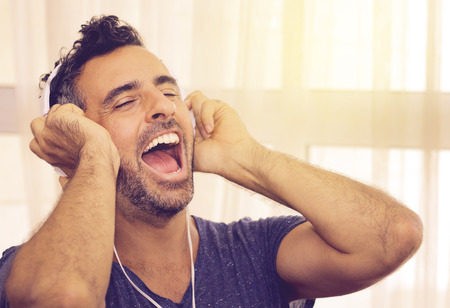 Exuberant handsome young man listening to his music cheering and singing along to the lyric and beat as he listens to the soundtrack on his headphones photo