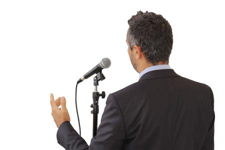 白い背景に、リーダーシップと国際会議のシンボルを指して、マイクで話す男性公共のスピーカーの背面に孤立