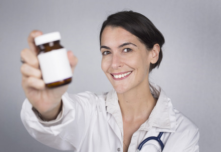 doctor holding gift: Doctor holding up a bottle of tablets or pills with a blank white label
