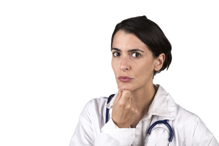 Worried female doctor in uniform looking seriously at the camera. Isolated on white. photo