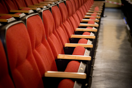 Oblique view over a row of red theatre seats at a movie theatre photo