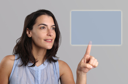 activating: Woman activating a blank rectangular navigation button with copyspace for your text on a virtual touch screen or interface with her finger in a concept of smart technology, access and connectivity Stock Photo