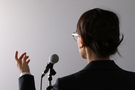 View from behind of a businesswoman standing in front of a microphone gesturing as she gives a presentation or speech
