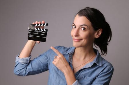 灰色のスタジオの背景でクラッパーを設定ジーンズ シャツ生産を保持している魅力的な女性を笑顔