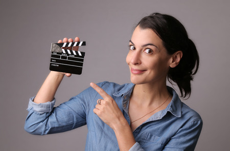 Smiling attractive woman in jeans shirt holding a production set clapper with gray studio background