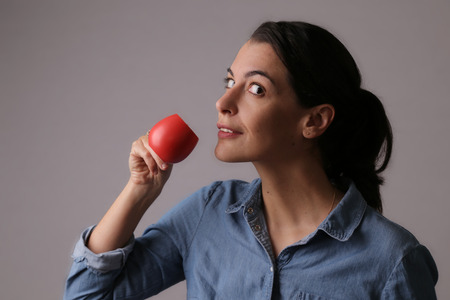 glancing: Close up Middle Age Woman Drinking Coffee from Small Red Cup While Glancing to the Camera. Isolated on Gray Background.