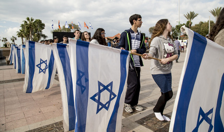 zionism: NETHANIA, ISRAEL - NOVEMBER 28, 2014 BNEI AKIVA youth group ceremony rehearsal with Israeli flags
