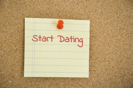 finding a mate: Dating Concept - Close up Start Dating Texts on Small Paper Pin on Brown Bulletin Board, Emphasizing Copy Space.