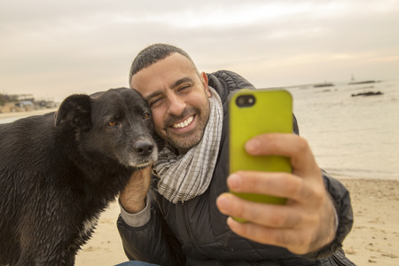 comunicacion no verbal: Hombre ayudar a su perro haciendo selfie imagen usando un teléfono inteligente