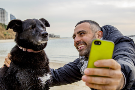 Man helping his grumpy dog firend to take a social media selfie image using a smartphone Standard-Bild